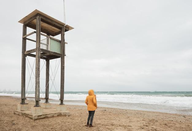 바다를보고 노란 우비에 여자. 날씨가 좋지 않은 날에는 해변을 따라 걸어보세요.