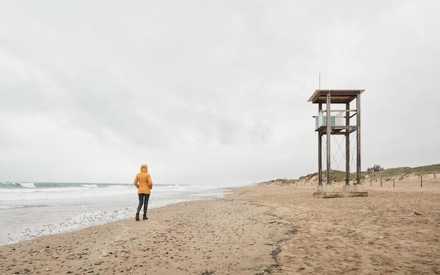 海を見ている黄色いレインコートの女性。悪天候の日にビーチに沿って歩きます。