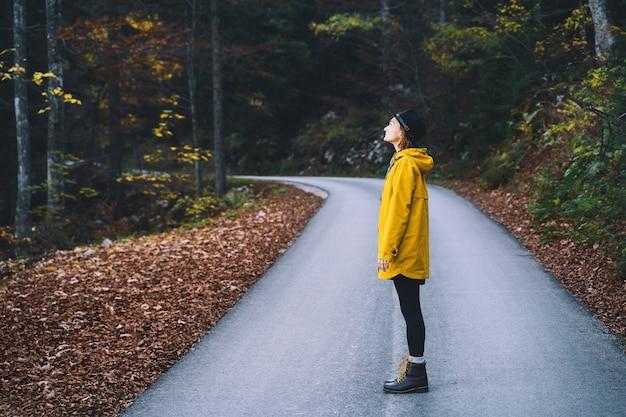 秋の森の道を歩いている黄色いレインコートの女性屋外の自然の中で若いハイカーの女の子