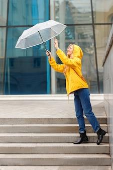 街の傘と黄色のレインコートの女性