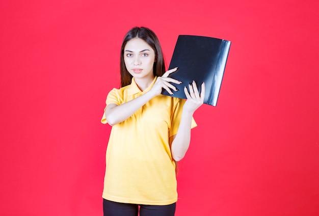 Женщина в желтой рубашке держит черную папку.