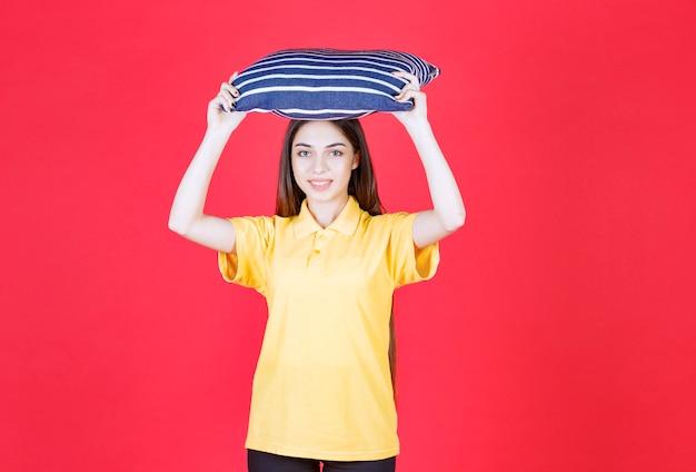 Женщина в желтой рубашке держит синюю подушку с белыми полосами и надевает голову.