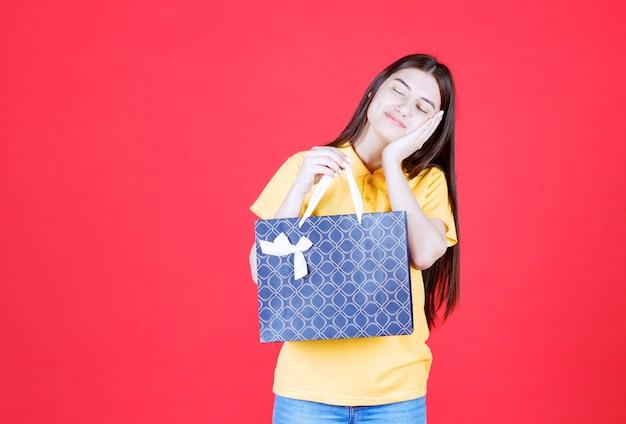 青い買い物袋を持っている黄色いシャツを着た女性は、疲れて眠そうに見えます。