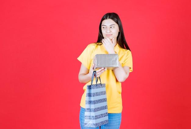 쇼핑 가방과 실버 선물 상자를 들고 노란색 셔츠에 여자와 혼란스럽고 사려 깊은 보인다.