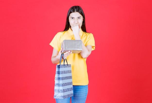 Женщина в желтой рубашке держит сумку для покупок и серебряную подарочную коробку и выглядит напуганной и напуганной.