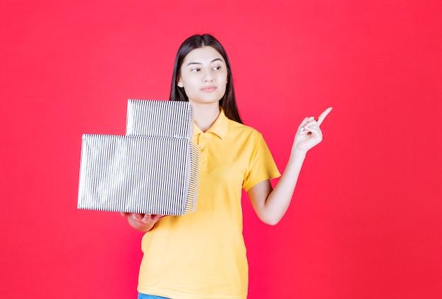 은색 선물 상자를 들고 노란색 셔츠에 여자 혼란과 사려 깊은 보인다.