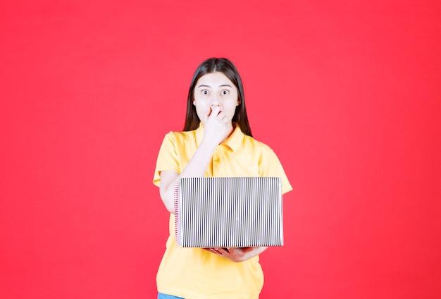 실버 선물 상자를 들고 노란색 셔츠에 여자와 무서 워 하 고 겁에 질 려 보인다.