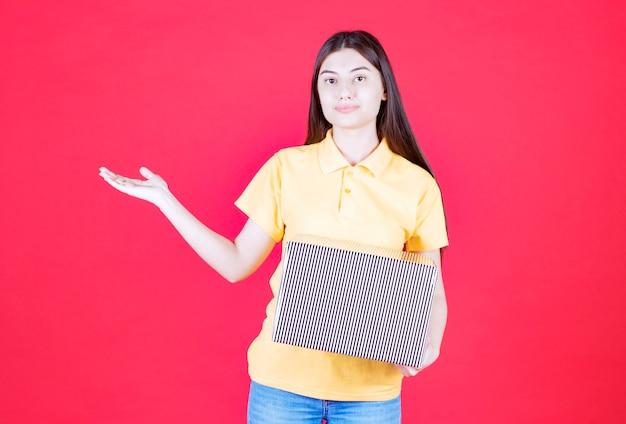 Женщина в желтой рубашке держит серебряную подарочную коробку.