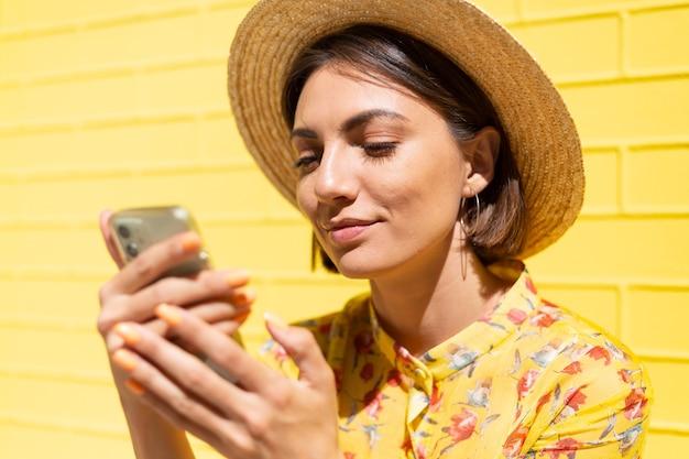 Женщина в желтом летнем платье и шляпе на желтой кирпичной стене спокойно и позитивно держит мобильный телефон