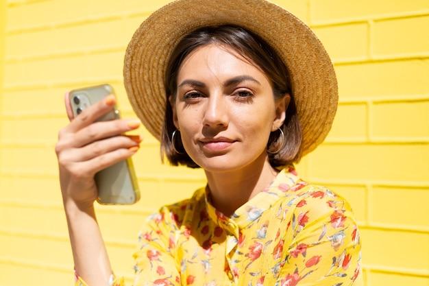 黄色い夏のドレスと黄色いレンガの壁に帽子をかぶった女性