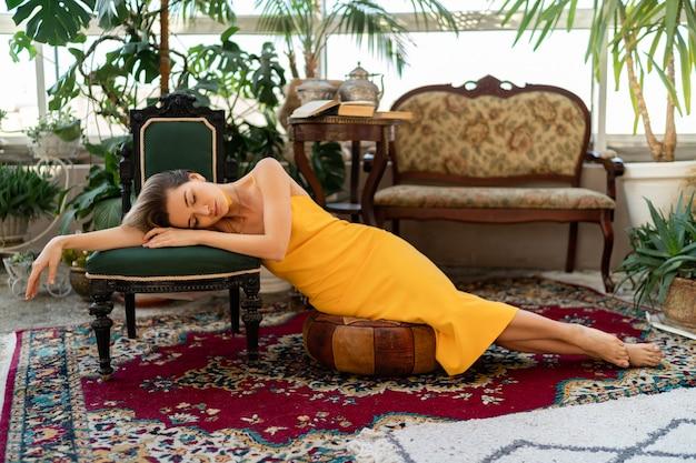 Женщина в желтом летнем платье с короткой прической в винтажном стиле бохо позирует в интерьере комнаты