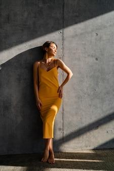 Женщина в желтом летнем платье с короткой прической в интерьере комнаты позирует с бетонной стеной
