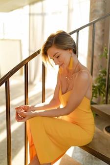 Женщина в желтом летнем платье с короткой прической сидит на лестнице позирует