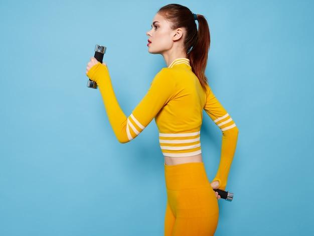 青い背景の側面図にダンベルと黄色のセーターとレギンスの女性