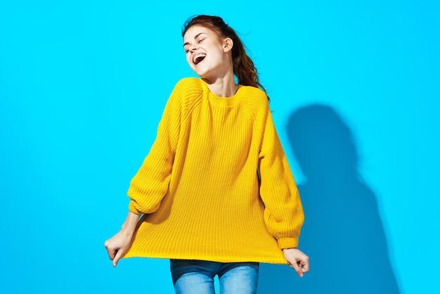 髪の青い背景ファッションを保持している黄色のセーターの女性