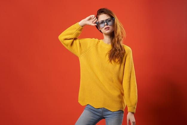 Женщина в желтом свитере позирует моде синие очки