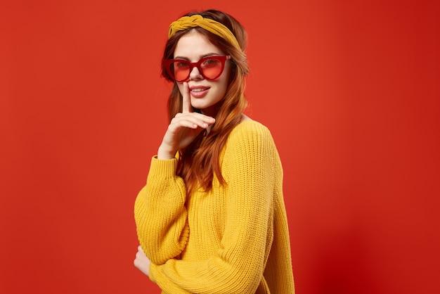 빨간 안경 머리띠 패션 빨간색 배경을 입고 노란색 스웨터에 여자