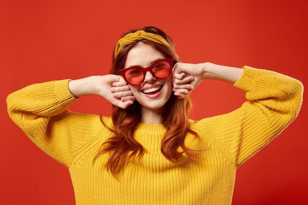 赤い眼鏡のヘッドバンドファッション赤い背景を身に着けている黄色のセーターの女性