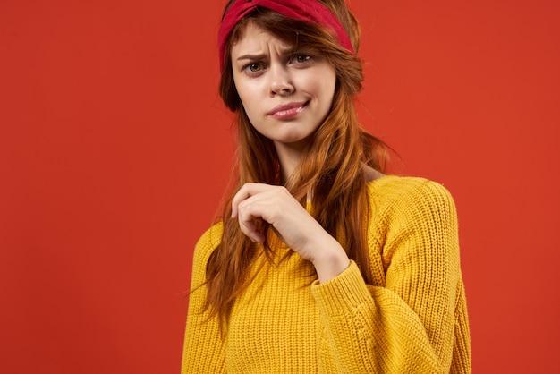 赤いヘッドバンドのファッションと黄色のセーターの女性。高品質の写真