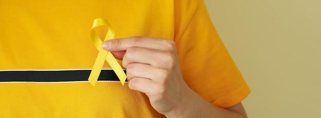 Женщина в желтой футболке держит детскую ленту осведомленности о раке