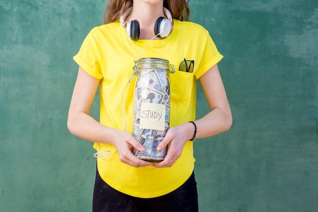 연구를 위해 저축한 병을 들고 노란색 티셔츠를 입은 여성