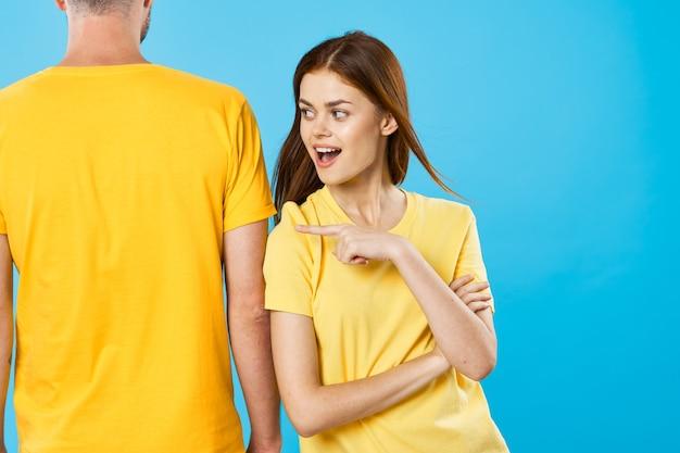 黄色のtシャツと青い背景の上の男性の背面図の女性