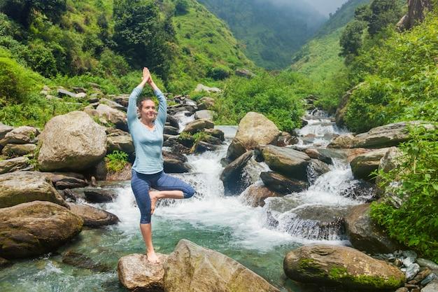 ヨガのアーサナvrikshasanaツリーの女性は屋外の滝でポーズします。