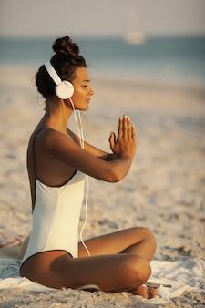 해변에서 헤드폰으로 요가 명상 포즈에 여자