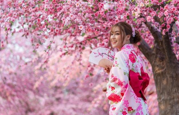 扇子を持って庭に咲く桜や桜を眺める浴衣姿の女性