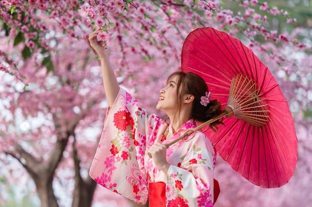 傘を持って庭に咲く桜の花や桜を眺める浴衣姿の女性