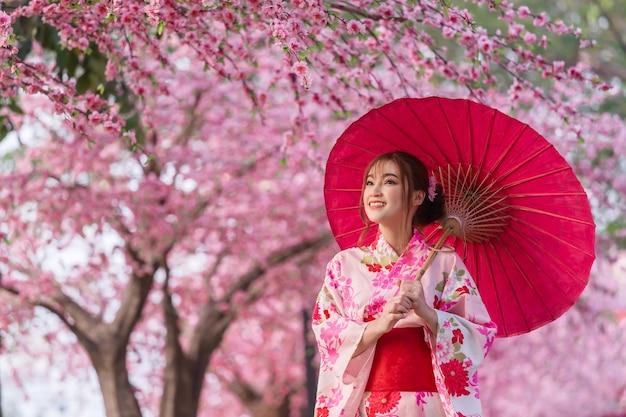 Женщина в юкате (платье кимоно) держит зонтик и смотрит цветок сакуры или цветущие вишни в саду