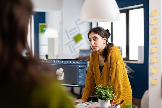 Woman industrial designer discussing with colleague standing at desk while working in cad program, designing 3d prototype of components