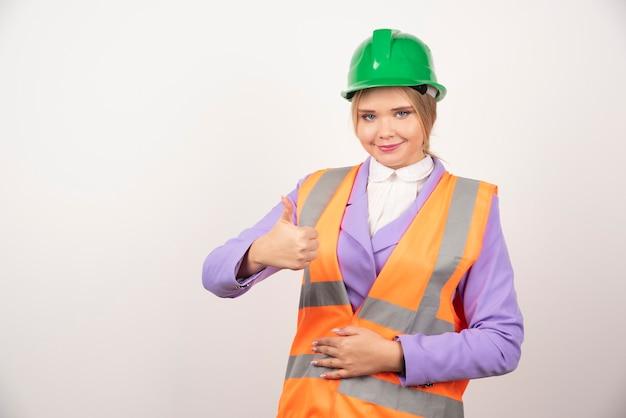 Impiegato industriale della donna che posa sul bianco.