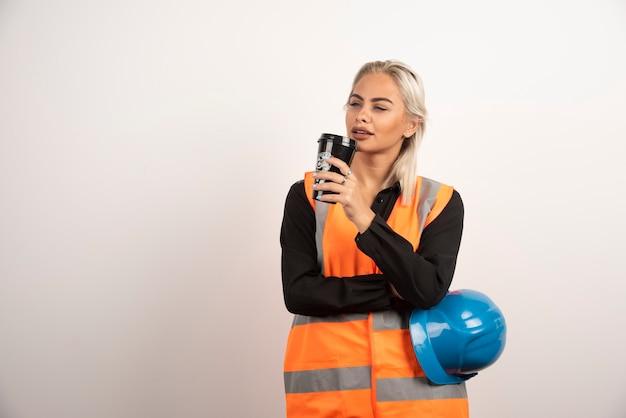그녀의 휴식 시간에 커피 한잔 마시는 여자 산업 노동자. 고품질 사진