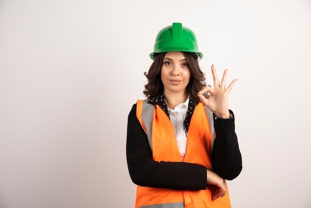 Промышленный рабочий женщина показывает знак ок на белом