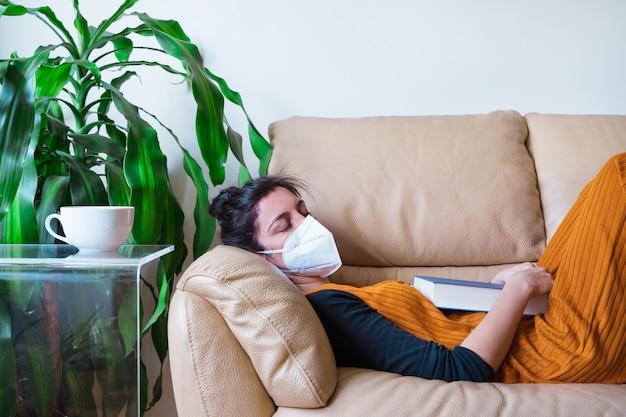 自宅のソファで寝ているコロナウイルス感染症の女性。家にいる。世界的なパンデミックウイルス病covid 19。