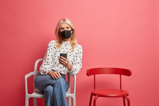 コロナウイルスに感染した女性は保護マスクを着用し、自己隔離で一人で携帯電話のチェックを使用しています