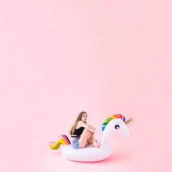 Woman on inflatable unicorn