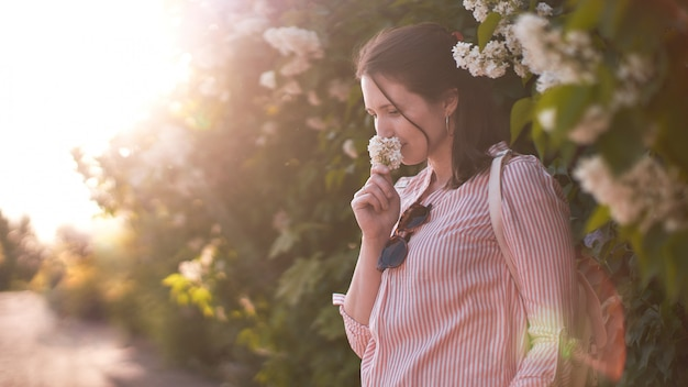 Woman inhales the fragrance of flowers in the sun
