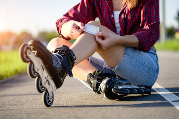 Woman injured knee while rollerblading. a teenager sticks a bruise with a band aid after falling while inline skating