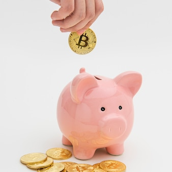 Woman inserting a bitcoin into a pink piggy bank