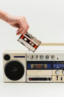 Woman inserting a cassette tape into a vintage radio