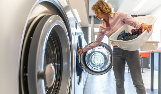 Woman inserting dirty clothes into the washing machine in the laundry room