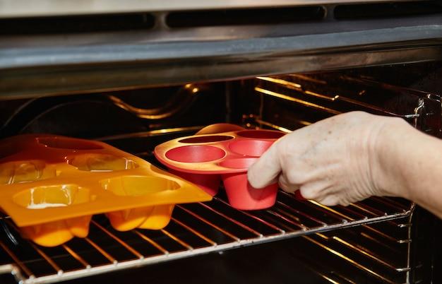 여성이 오븐에 머핀 통을 넣고 햇볕에 말린 토마토 머핀을 굽습니다.