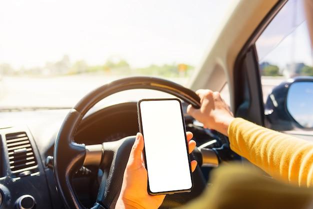 車の中で女性と車を運転中に携帯スマートフォンの空白の画面を持っている手を使用して