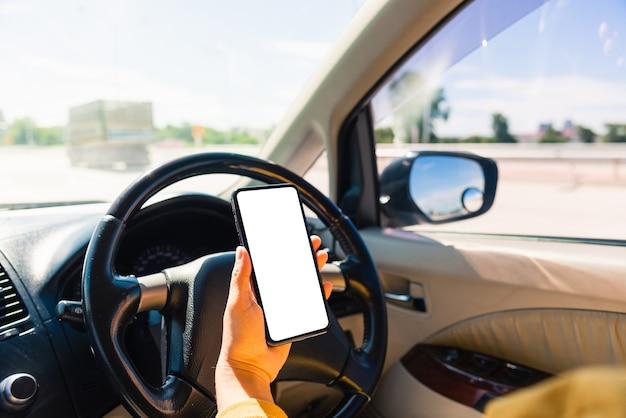 차 안에서 여자와 차를 운전하는 동안 손을 잡고 모바일 스마트 폰 빈 화면을 사용