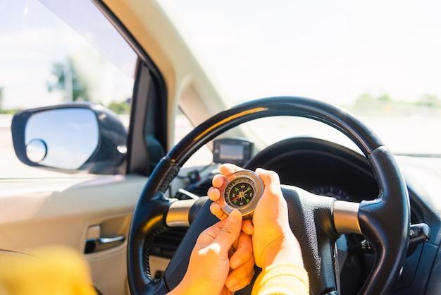 車内でコンパスを使用して車を運転しながらナビゲートする女性