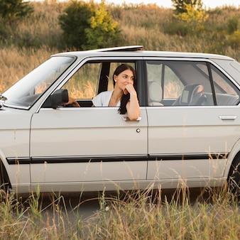 Donna all'interno dell'auto in posa nel campo