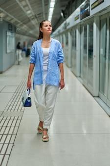 Женщина в метро ждет поезда на платформе железнодорожного вокзала.