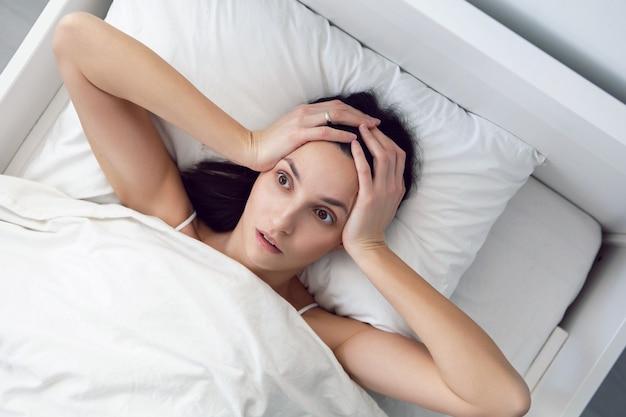 흰색 티셔츠에 여자 불면증이 침대에 누워 있고 베개는 방의 담요 아래에 있습니다.